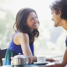 Smiling couple having tea outdoors